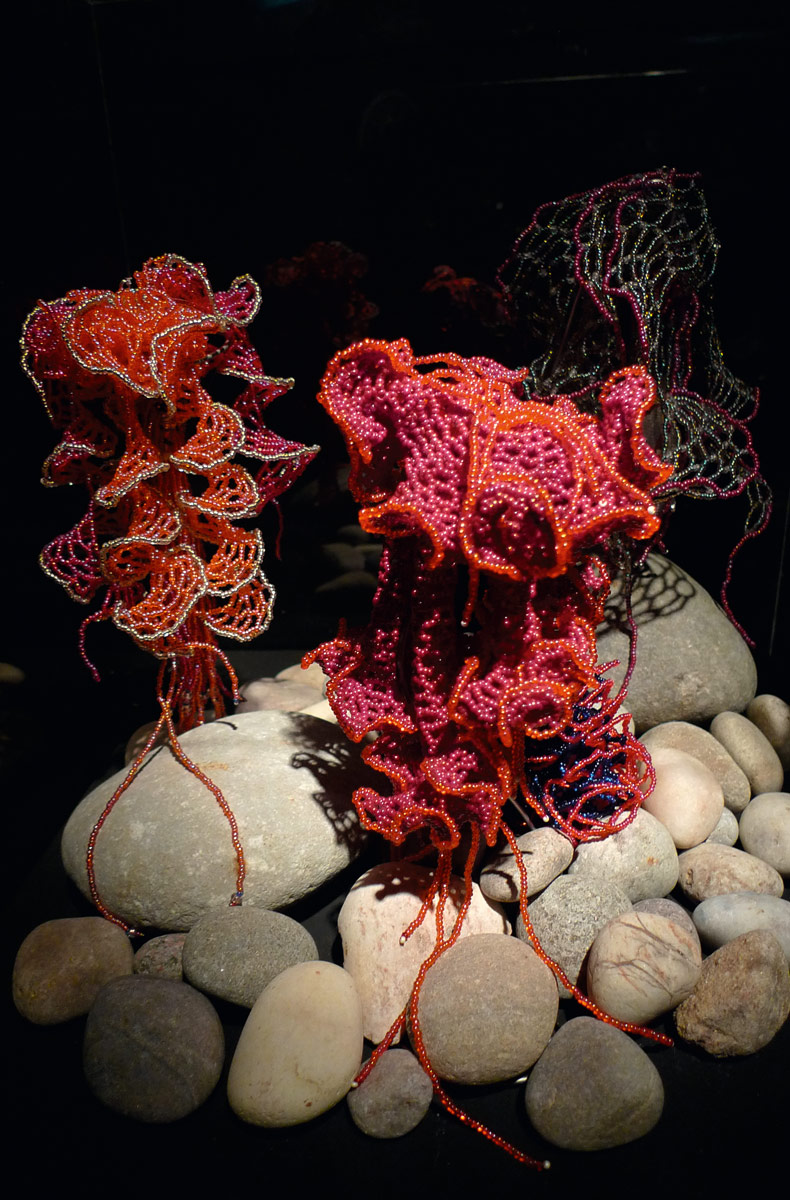 Coral reef made from beads on top of smooth stones and a dramatic black background.