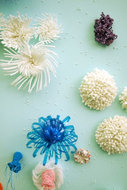 Detail of crochet coral sculpture in front of blue wall.