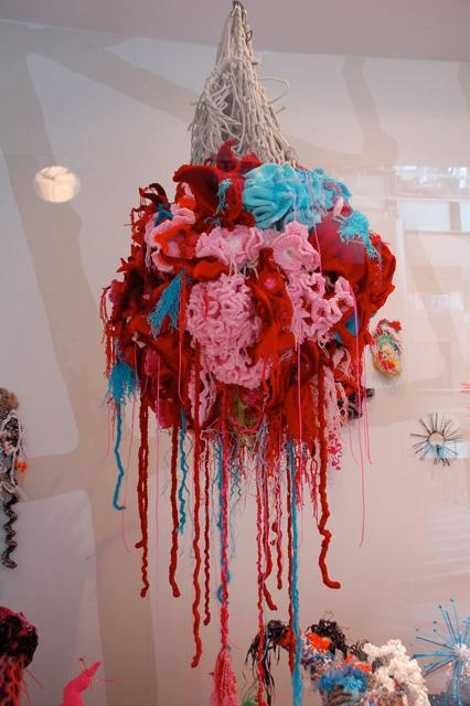 Detail of crochet coral reef sculpture hanging in window.