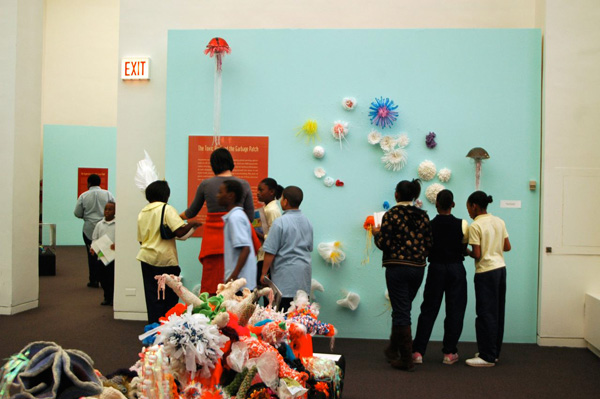 People looking at crochet sculptures on gallery wall.