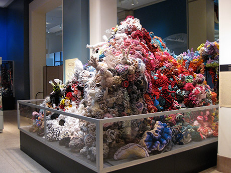 Large crochet coral reef sculpture stacked in a pyramidal form.