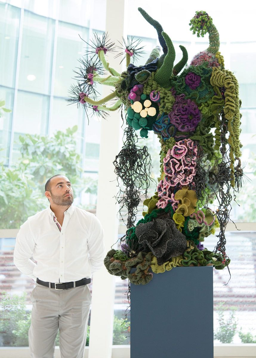 Man looking at large sculpture of crochet coral reef