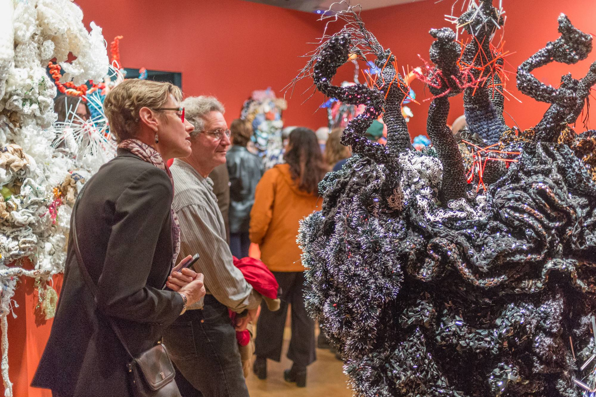 people standing among and looking at sculptures of a giant coral forest
