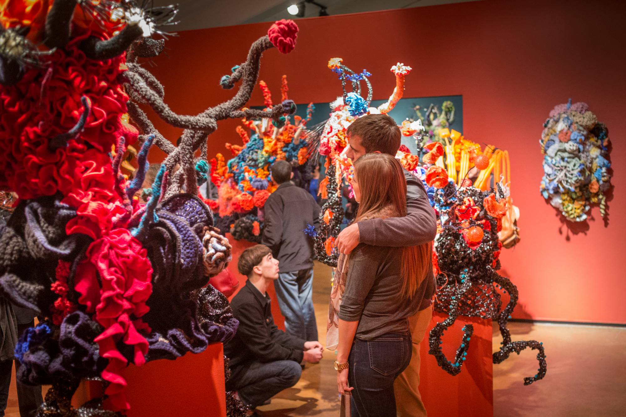 Museum visitors cuddle among a series of giant woolen coral forest sculptures
