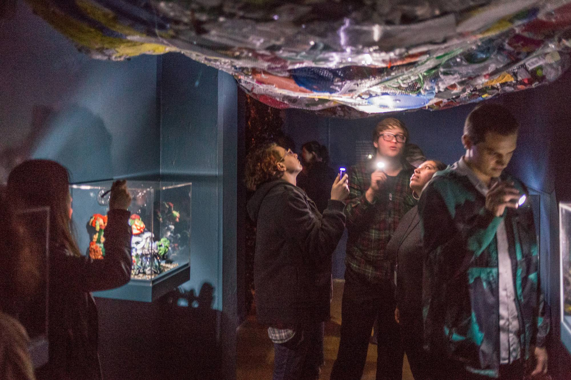 Museum visitors under a giant net filled with plastic trash. They are illuminating the trash with spotlights as if they are under the sea.