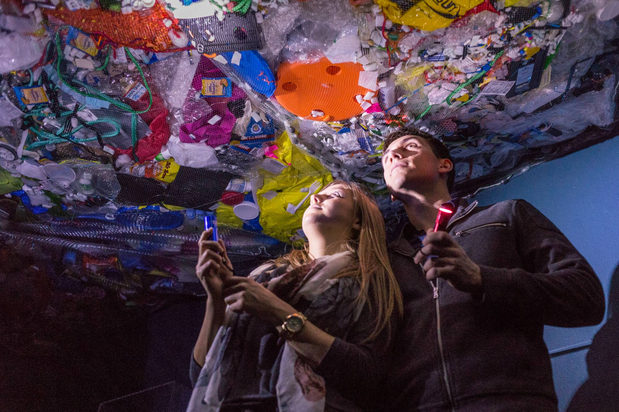 Two people stand underneath a net filled with trash