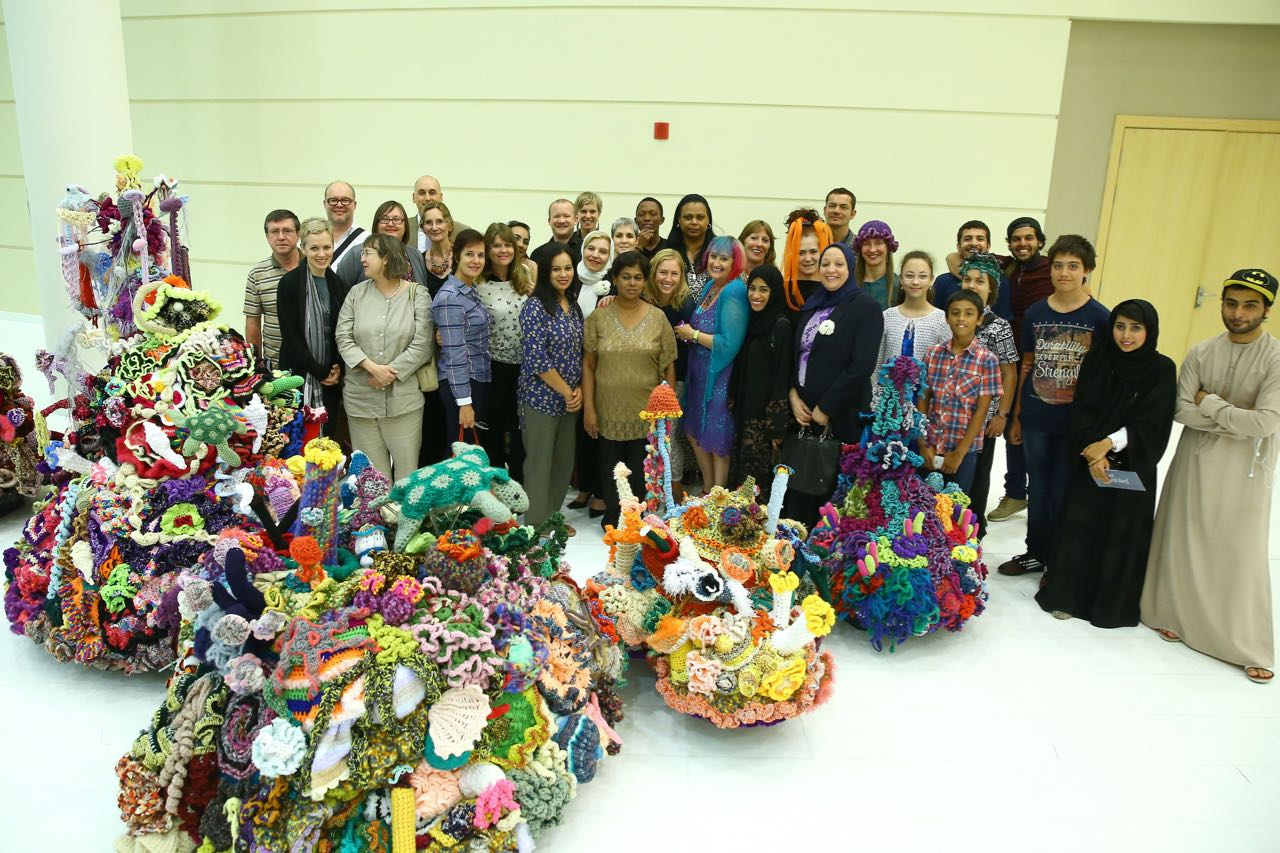 Volunteer crocheters posing for a photograph in front of crochet coral reef sculpture