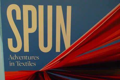 A wall that features the title of the exhibition, SPUN: Adventures in Textiles