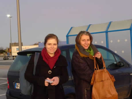 Two young women stand in front of a car.