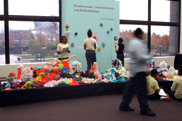 People looking at crochet sculptures in large gallery.