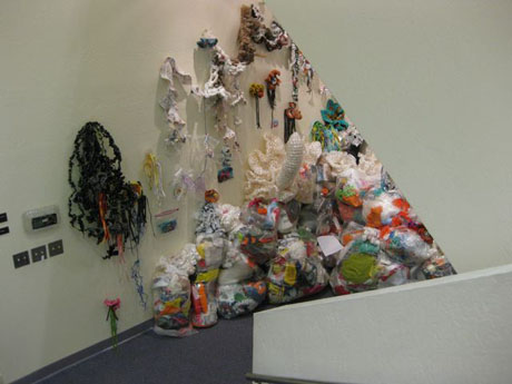 Installation view of plastic trash artwork installed in corner of the gallery.