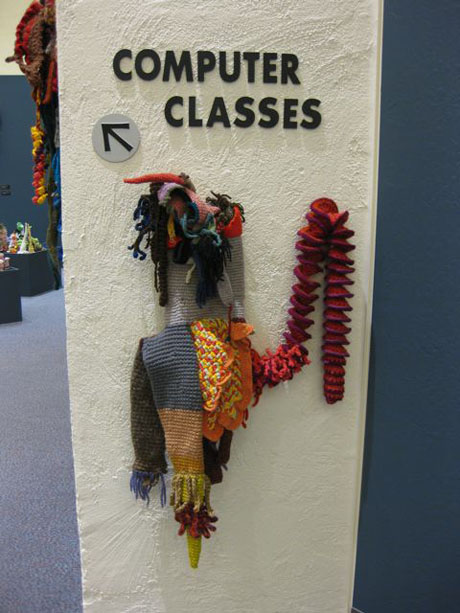 Crochet coral reef sculpture hanging on wall underneath