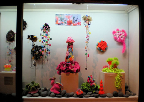 Crochet coral reef sculptures installed in a vitrine.