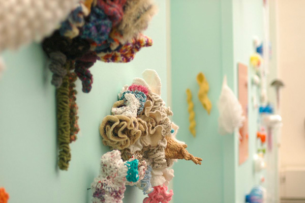 Detail of crochet coral sculptures installed on wall. .