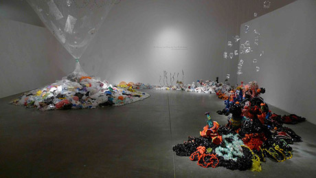 Installation view of crochet coral reef sculptures in white-walled gallery.