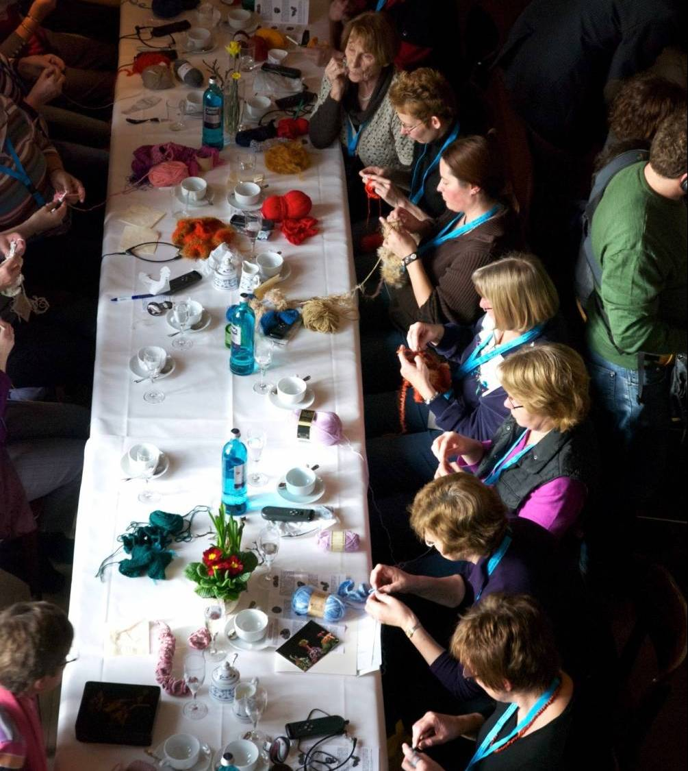 A group of people sitting at a long table crocheting