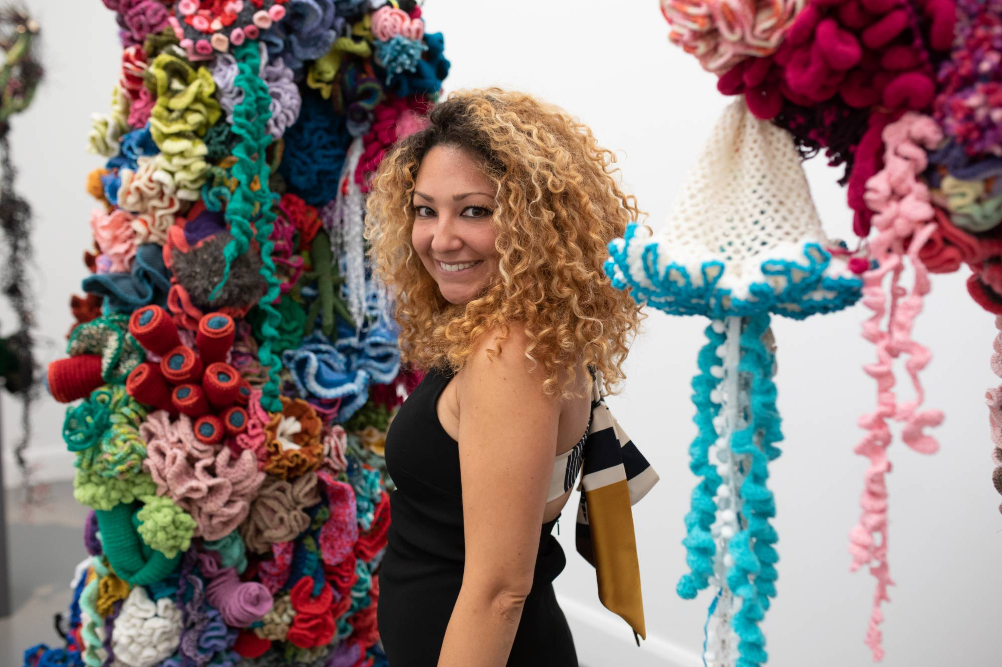 Smiling woman in front of colorful reef sculptures