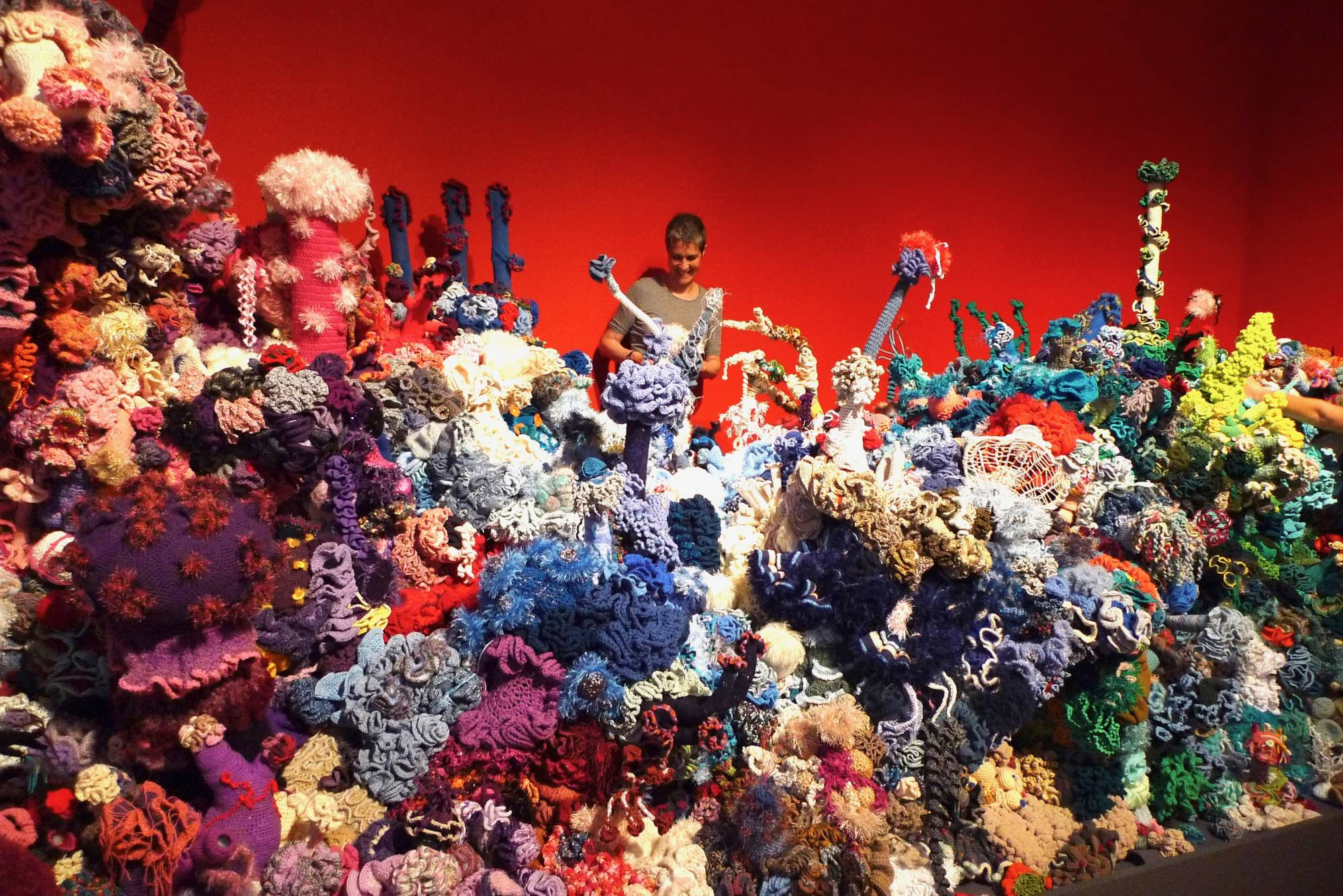 Person standing in a giant room of crocheted coral