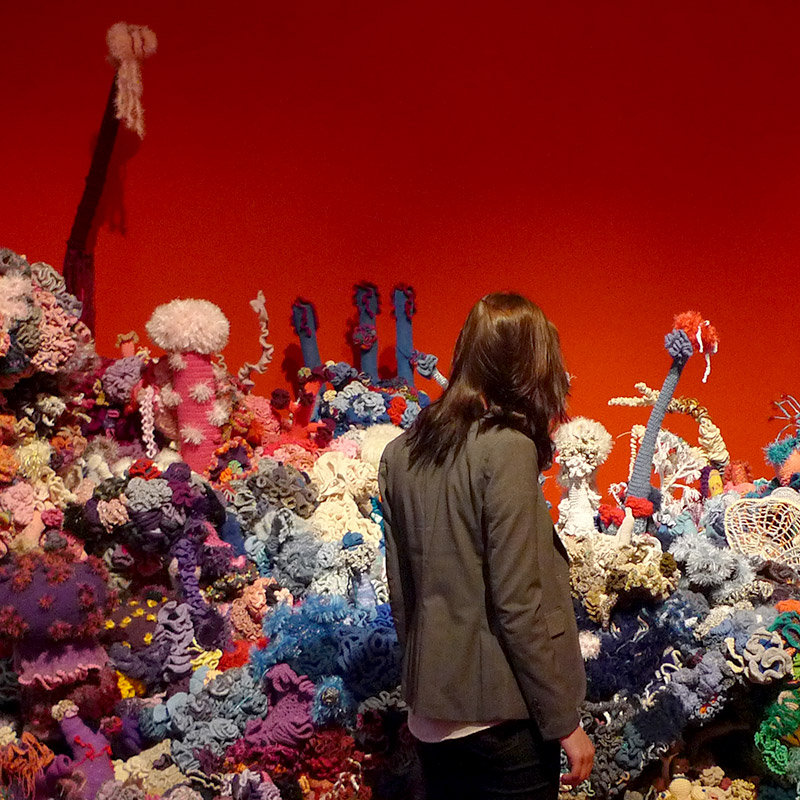 Person standing amid a sea of reef sculptures in a gallery