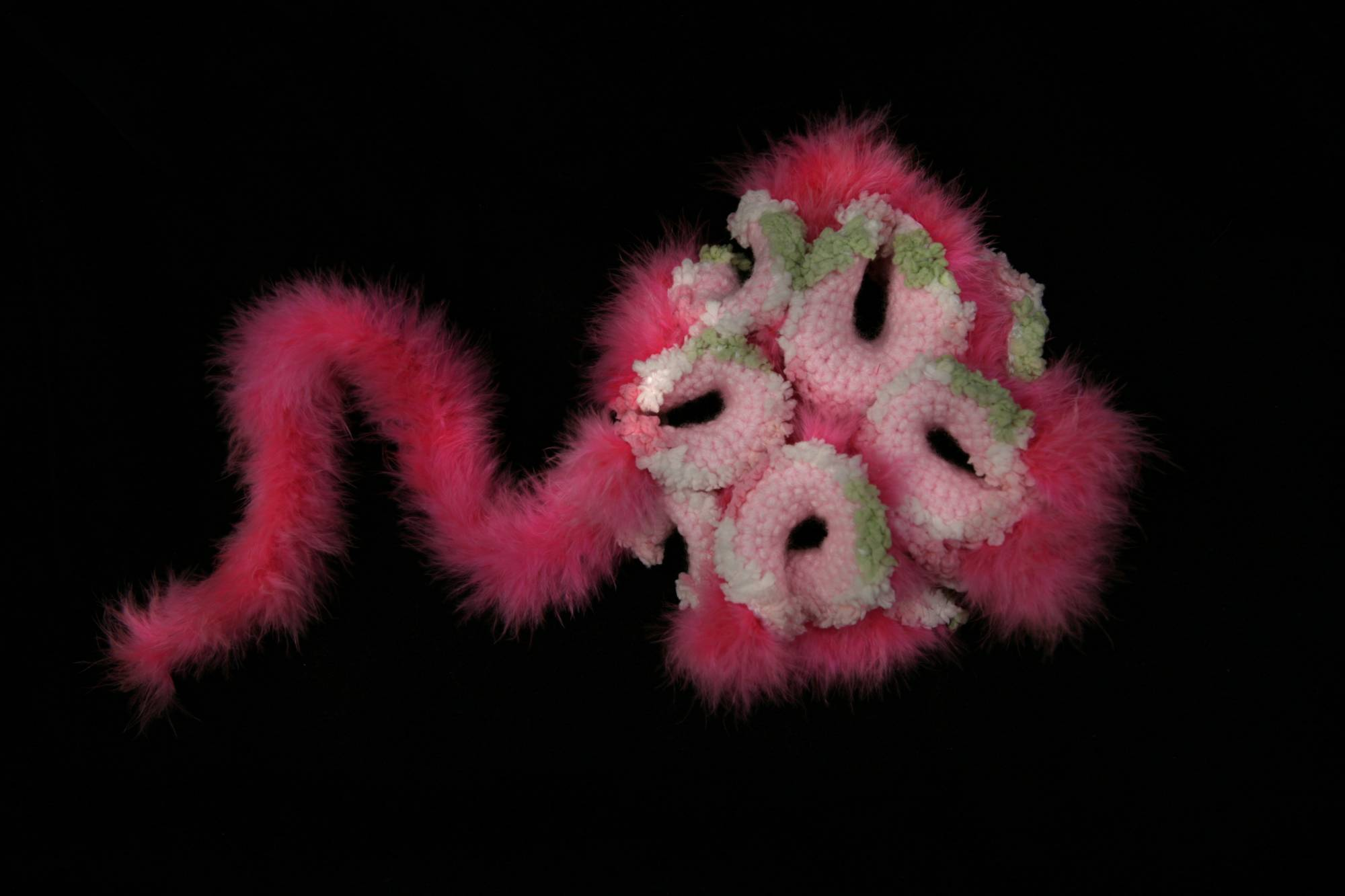 Pink sea creature looks like a surreal jellyfish with a hot pink fluffy tail
