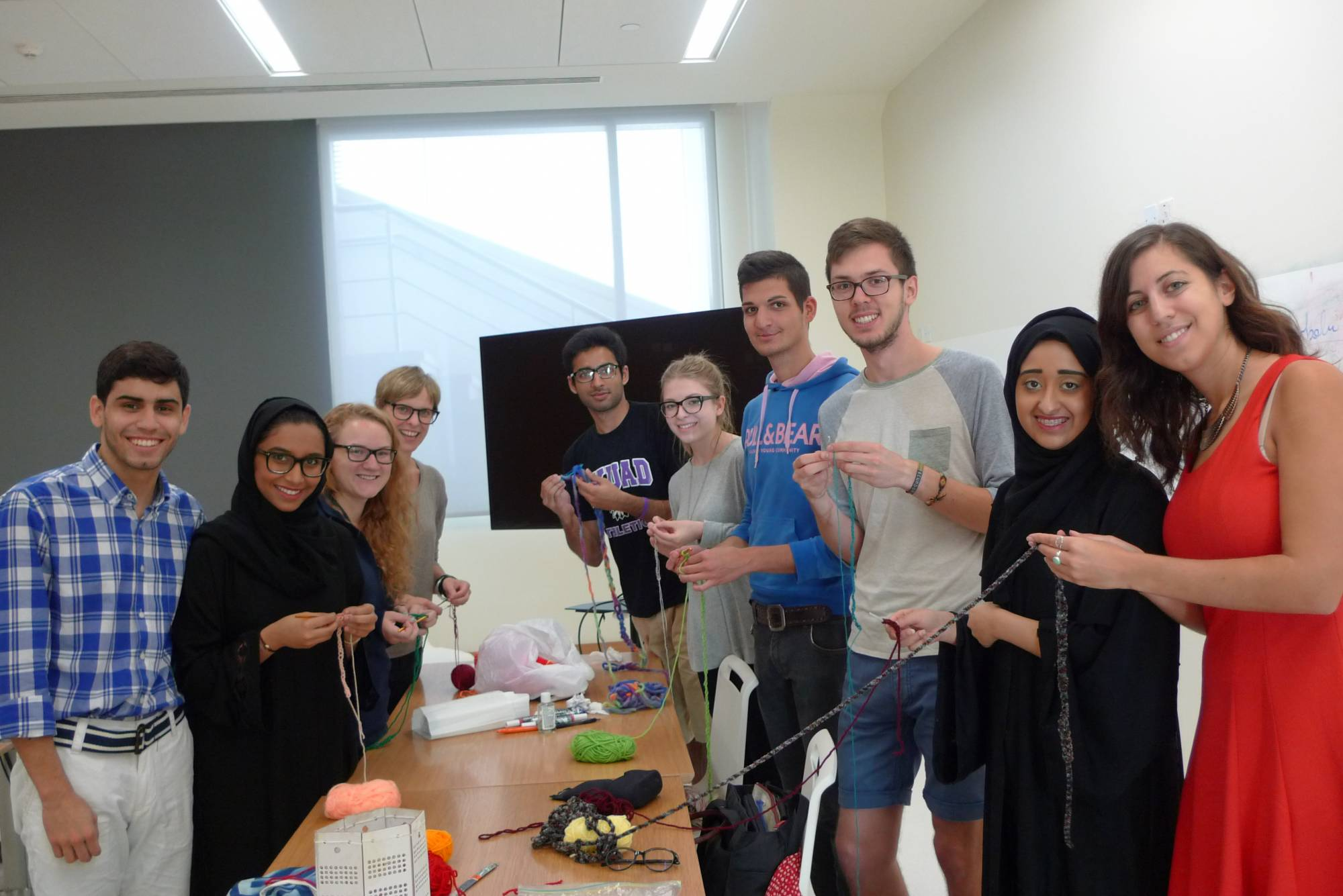 young women and men crocheting, some of the women are wearing the hijab