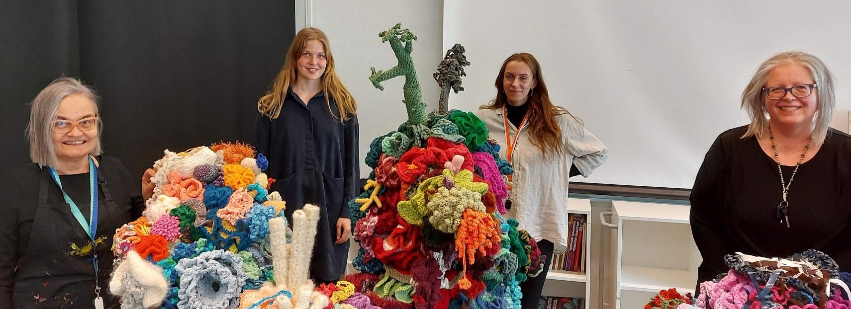 Women constructing crochet coral reefs