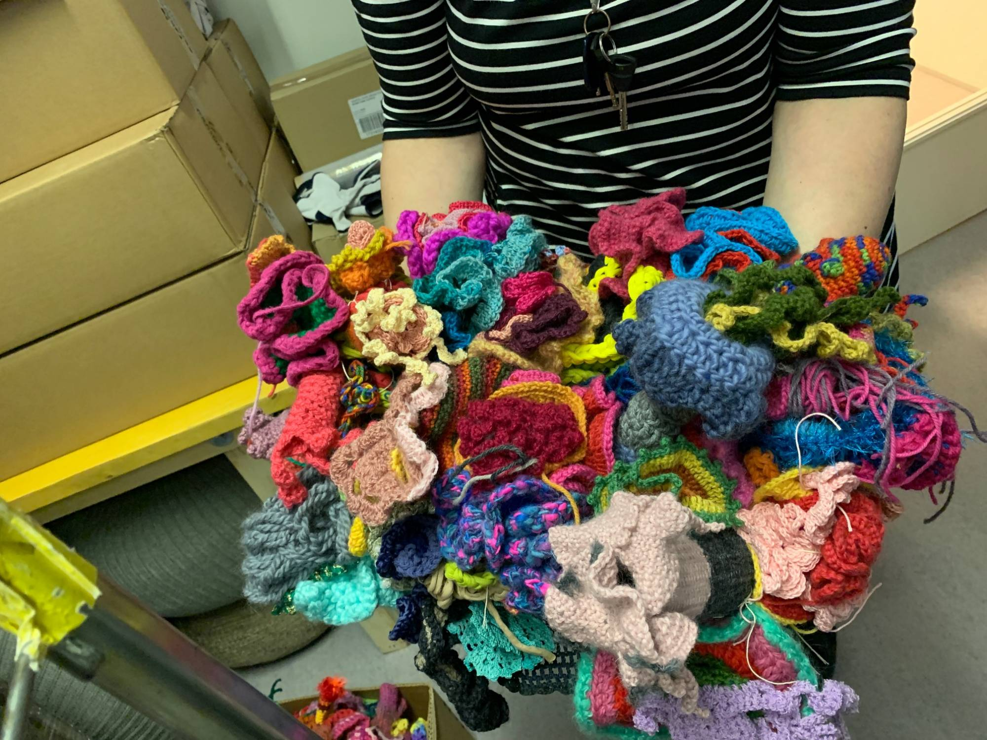 Hands holding a mound of crochet corals