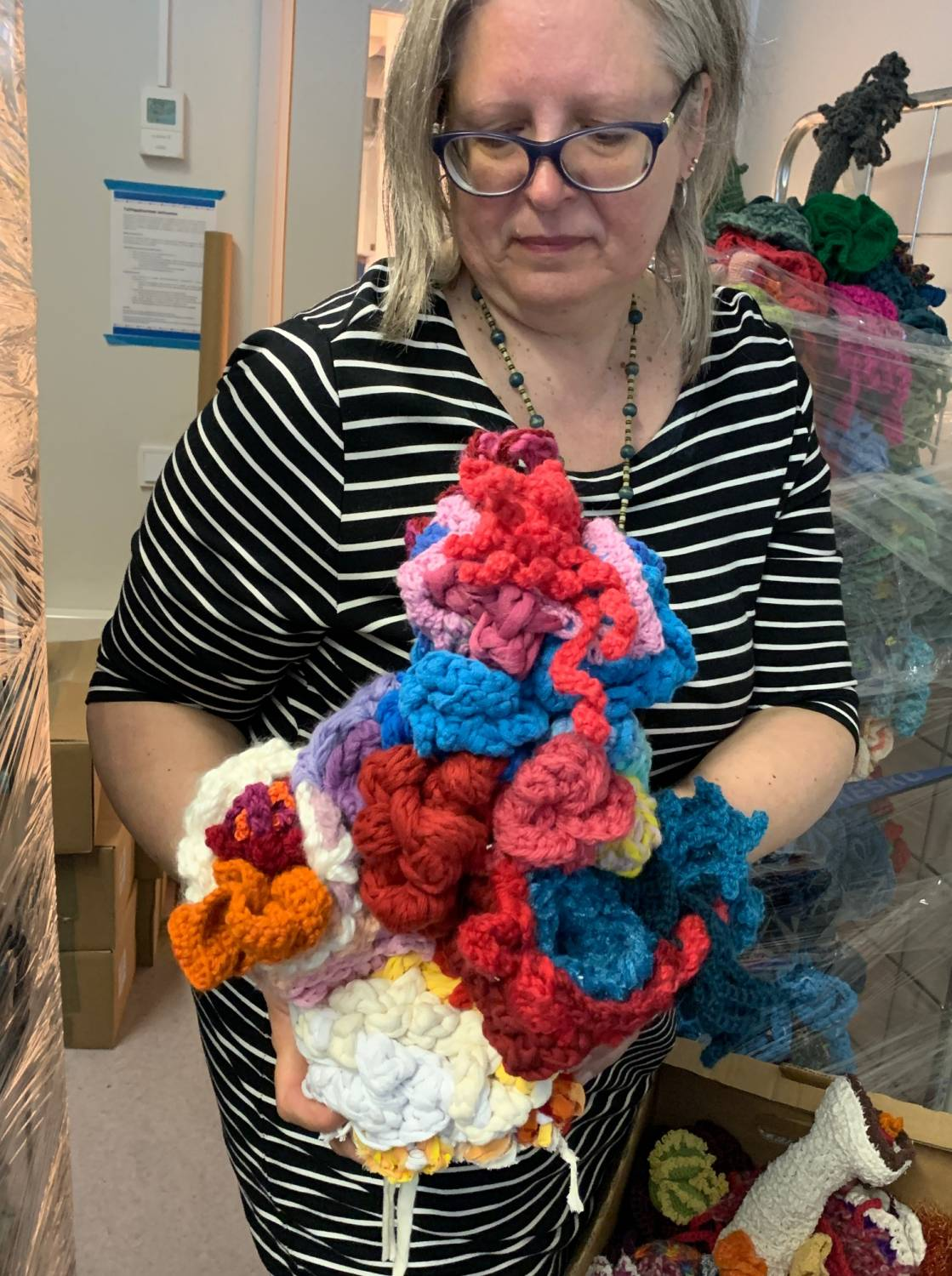 Woman holding a mound of crochet corals
